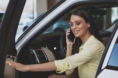 Привлекательная женщина используя ее умный телефон пока bying новый автомобиль стоковые фотографии rf