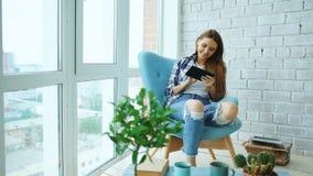 Привлекательная женщина используя цифровую таблетку сидя в стуле на балконе в квартире просторной квартиры современной Стоковая Фотография
