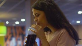 Привлекательная женщина наслаждаясь, выпивать сладкая вода соды и усмехаясь в камеру сток-видео