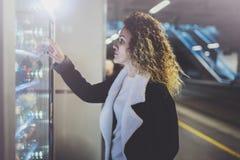 Привлекательная женщина на платформе перехода используя современный торговый автомат напитка Ее рука помещена на пусковой площадк стоковые фото