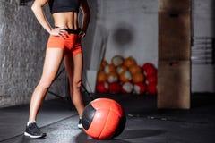 Привлекательная женщина нося красные брюки и черную верхнюю часть представляя с шариком медицины стоковые изображения rf