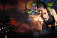 Привлекательная женщина пригонки разрабатывает с гантелями как фитнес схематический над темной предпосылкой Женщина фитнеса в тре стоковое фото