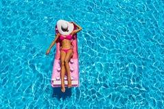 Привлекательная женщина расслабляющая на плавая тюфяке в бассейне стоковое изображение rf