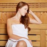Привлекательная женщина сидя в sauna Стоковые Фото