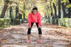 Привлекательная женщина спорта в задыхаться sportswear бегуна дышая и принимать пролом утомлянный и вымотанный после идущей разми Стоковое Изображение RF