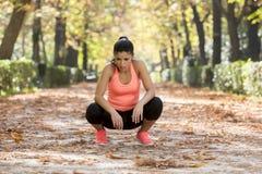 Привлекательная женщина спорта в задыхаться sportswear бегуна дышая и принимать пролом утомлянный и вымотанный после идущей разми Стоковое Фото