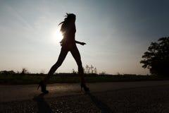 Привлекательная женщина с длинным - силуэт против света солнца стоковое фото rf
