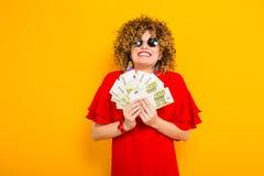 Привлекательная женщина с коротким вьющиеся волосы с наличными деньгами Стоковые Изображения RF