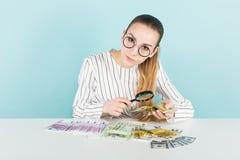 Привлекательная женщина с наличными деньгами и лупой Стоковое Фото