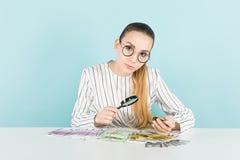 Привлекательная женщина с наличными деньгами и лупой Стоковые Изображения RF