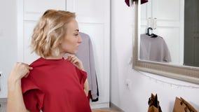Привлекательная женщина с расчалками пробует на новой футболке сток-видео
