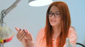 Привлекательная женщина redhead смотрит ее новые маникюр и улыбку Стоковая Фотография