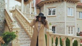 Привлекательная излучающая молодая женщина брюнет, носит стильное пальто и шляпа, имеет длинное вьющиеся волосы, закручивает, пре акции видеоматериалы