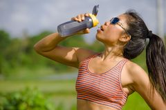 Привлекательная и подходящая азиатская женщина бегуна держа изотонную питьевую воду бутылки после тренировки и бежать разминки се стоковые фото
