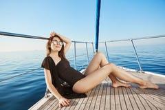 Привлекательная кавказская девушка на каникулах, загорая на частной яхте держа руку на голове, довольный и расслабленный bozo стоковые изображения rf