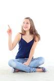 Привлекательная кавказская девушка сидя на поле указывая с перстом Стоковое Изображение