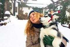 Привлекательная кавказская женщина обнимает смешную собаку malamute нося antlers рождества santa дорогие Курчавая усмехаясь женщи стоковое фото rf