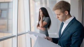 Привлекательная коммерсантка говоря на телефоне, бизнесмен смотря проект стоя в компании видеоматериал