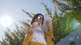 Привлекательная коммерсантка работая на планшете во время перерыва на ланч около центра офиса outdoors Концепция видеоматериал