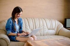 Привлекательная компьтер-книжка usig дамы на кожаной софе стоковое фото