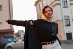 Привлекательная красивая молодая женщина в стильной футболке в пальто в винтажных джинсах отдыхая outdoors в городе стоковое изображение