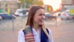 Привлекательная маленькая девочка, в вечере в центре города, получает сообщение на ее смартфоне с хорошими новостями и сток-видео