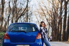 Привлекательная маленькая девочка на дороге около автомобиля Стоковое Изображение RF