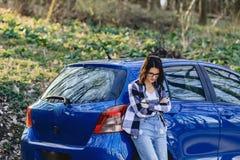 Привлекательная маленькая девочка на дороге около автомобиля Стоковые Изображения RF