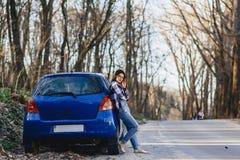 Привлекательная маленькая девочка на дороге около автомобиля Стоковое Фото