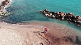 Привлекательная маленькая девочка на песчаном пляже Платье развевая женщины ветра на пляже Милая женщина идя через пляж с белым п сток-видео