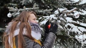Привлекательная маленькая девочка с длинными волосами в костюме зимы представляя против снежного дерева Девушка шнурует шарики ро видеоматериал