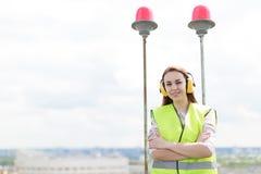 Привлекательная милая женщина работника в зеленом западе и earmuffs стоят на крыше, держат таблетку Стоковое Изображение RF