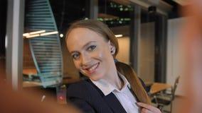 Привлекательная милая молодая женщина принимая selfie в офисе в большом городе видеоматериал