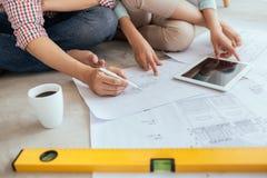 Привлекательная молодая азиатская взрослая пара смотря дом планирует Стоковое Изображение