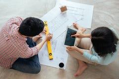 Привлекательная молодая азиатская взрослая пара смотря дом планирует Стоковые Изображения RF