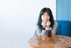Привлекательная молодая азиатская женщина усмехаясь за чашкой americano кофе льда на деревянном столе с космосом текста экземпляр стоковое изображение