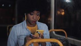 Привлекательная молодая Афро-американская женщина используя смартфон ехать на общественном транспорте Nighttime Предпосылка свето акции видеоматериалы