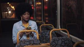 Привлекательная молодая Афро-американская женщина используя смартфон ехать на общественном транспорте и смотря вне окно r видеоматериал