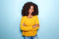 Привлекательная молодая Афро-американская женщина стоя с ее оружиями пересекла на голубую предпосылку стоковая фотография