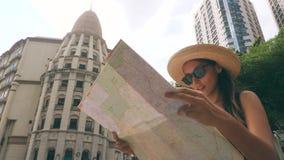 Привлекательная молодая девушка битника проверяя направления на карте города и идя на старую улицу 4k, замедленное движение акции видеоматериалы