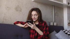 Привлекательная молодая девушка брюнет усмехаясь и перечисляя smartphone видеоматериал