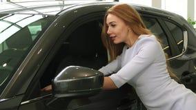 Привлекательная молодая женщина выбирая новый автомобиль на салоне дилерских полномочий сток-видео