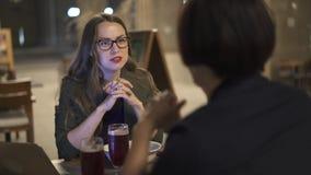 Привлекательная молодая женщина в стеклах говоря к ее другу в кафе ночи outdoors видеоматериал