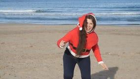 Привлекательная молодая женщина в танцах шляпы Санта Клауса и потехе иметь на пляже видеоматериал