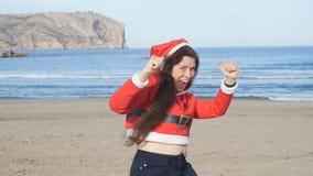 Привлекательная молодая женщина в танцах шляпы Санта Клауса и потехе иметь на пляже акции видеоматериалы