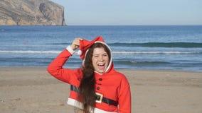 Привлекательная молодая женщина в танцах шляпы Санта Клауса и потехе иметь на пляже сток-видео