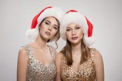 Привлекательная молодая женщина 2 в шляпах santa стоковые фотографии rf