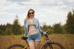 Привлекательная молодая женщина в sportswear в поле цветка с велосипедом стоковые фото