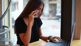 Привлекательная молодая женщина говоря на телефоне в кафе работая с компьтер-книжкой во время ее перерыва на чашку кофе сь женщин сток-видео