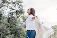 Привлекательная молодая женщина идущ снаружи создает программу-оболочку в теплом одеяле стоковое фото rf